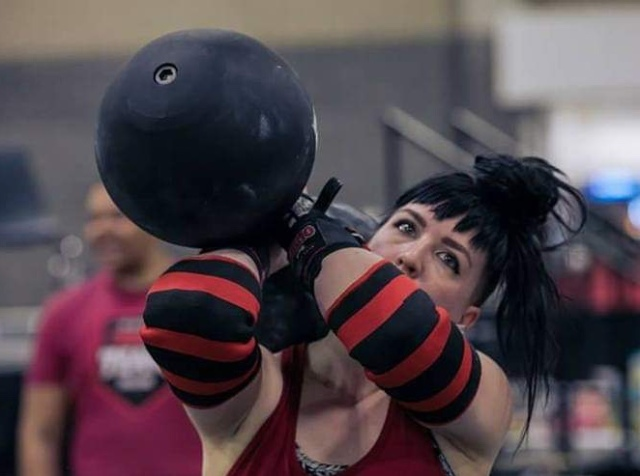 The author holds a giant lifting dumbbell to one shoulder, preparing to press it overhead with one arm.